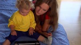Mulher do baby-sitter que ensina a menina pequena da criança que usa o PC da tabuleta que senta-se na cama video estoque