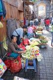Mulher do Balinese nas pétalas da flor da venda do mercado para o oferecimento diário Imagens de Stock Royalty Free