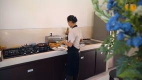 Mulher do Balinese que cozinha o café da manhã na cozinha video estoque