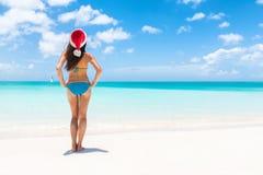 Mulher do biquini do chapéu de Santa da praia do Natal que relaxa imagem de stock royalty free