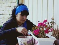 A mulher do cabelo escuro é semear flores Imagem de Stock