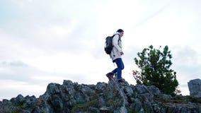 A mulher do caminhante aprecia o curso que backpacking nas montanhas vídeos de arquivo