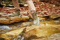 Mulher do caminhante que cruza um córrego, ideia dos pés Fotografia de Stock Royalty Free