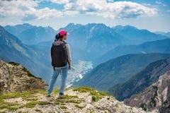 Mulher do caminhante que está acima de realização os cumes superiores das dolomites fotos de stock