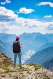 Mulher do caminhante que está acima de realização os cumes superiores das dolomites foto de stock royalty free