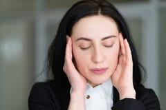 Mulher do cansaço do esforço da dor de cabeça que faz massagens templos imagens de stock