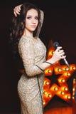 Mulher do cantor no vestido 'sexy' do brilho na fase com a estrela de broadway no fundo Penteado encaracolado, composição perfeit imagens de stock