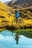 Mulher do ciclista em mountais da altura Imagem de Stock