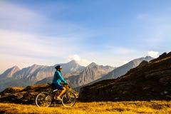 Mulher do ciclista em mountais da altura Foto de Stock Royalty Free