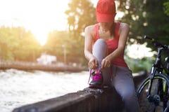 Mulher do ciclista que senta e que amarra o shoeslace ao longo do canal no por do sol Foto de Stock