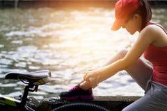 Mulher do ciclista que senta e que amarra o shoeslace ao longo do canal no por do sol Imagens de Stock Royalty Free