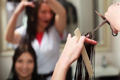 Mulher do cliente do cabelo do corte do barbeiro no salão de beleza Imagens de Stock