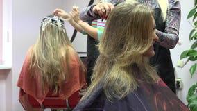 A mulher do cliente novo faz o penteado novo no cabeleireiro da beleza 4K vídeos de arquivo
