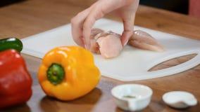 A mulher do close-up corta a faixa da galinha com uma faca cerâmica em uma placa de madeira A fêmea entrega o cozinheiro chefe qu video estoque