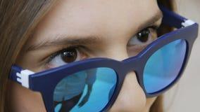 A mulher do close up em óculos de sol azuis do espelho fala e sorri vídeos de arquivo