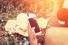 A mulher do close-up entrega usando o smartphone à colocação de escuta da música Imagem de Stock Royalty Free