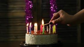 A mulher do close-up ilumina velas no bolo de aniversário saboroso Movimento lento vídeos de arquivo
