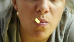 Mulher do close-up que come a comida lixo com grande apreciação a menina come batatas fritas Movimento lento vídeos de arquivo