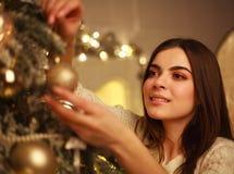 A mulher do close up que decora o ` s do ano novo de árvore de Natal brinca em casa Fotos de Stock Royalty Free