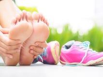 Mulher do close up que faz massagens seu pé doloroso ao exercitar fotos de stock