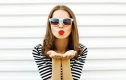 Mulher do close-up do retrato que funde os bordos vermelhos que enviam o beijo doce do ar na parede branca imagens de stock royalty free