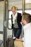 Mulher do compartimento do trem do assento do homem que obtem dentro Fotografia de Stock Royalty Free
