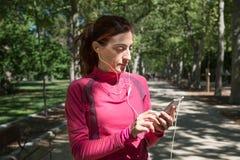 Mulher do corredor que usa o móbil com fones de ouvido da orelha Fotografia de Stock Royalty Free