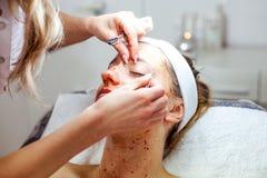 A mulher do Cosmetologist está fazendo a modelagem da sobrancelha para a mulher/menina pela cera para o epilation Clínica de Cosm Imagens de Stock Royalty Free