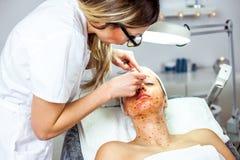 A mulher do Cosmetologist está fazendo a modelagem da sobrancelha para a mulher/menina pela cera para o epilation Clínica de Cosm Foto de Stock Royalty Free