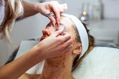 A mulher do Cosmetologist está fazendo a modelagem da sobrancelha para a mulher/menina pela cera para o epilation Clínica de Cosm Fotos de Stock
