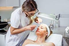 A mulher do Cosmetologist está fazendo a modelagem da sobrancelha para a mulher/menina pela cera para o epilation Clínica de Cosm Fotos de Stock Royalty Free