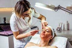 A mulher do Cosmetologist está fazendo a modelagem da sobrancelha para a mulher/menina pela cera para o epilation Clínica de Cosm Imagem de Stock Royalty Free