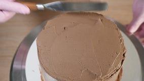 A mulher do cozinheiro chefe de pastelaria est? manchando o creme do chocolate no bolo de esponja filme