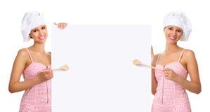 Mulher do cozinheiro chefe que aponta com uma colher de madeira no quadro de avisos branco Imagem de Stock Royalty Free