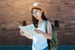 Mulher do curso de turista que olha o mapa ao andar em uma rua fotografia de stock