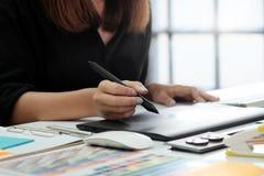 A mulher do designer gráfico que trabalha no escritório criativo com cria a GR Fotografia de Stock