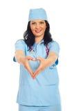 Mulher do doutor que dá forma à forma do coração Fotografia de Stock Royalty Free