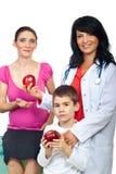 Mulher do doutor que dá maçãs a uma família Fotografia de Stock Royalty Free