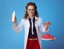 Mulher do doutor que mostra as sapatilhas da aptid?o e o pulverizador do desinfetante da sapata fotos de stock
