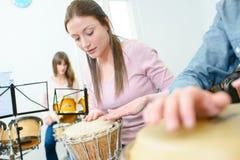Mulher do ensaio da música que joga bongos fotografia de stock royalty free