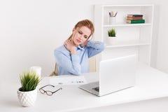 Mulher do escritório que senta-se na frente do computador em seus local de trabalho e neckache de sentimento Trabalhador triste S foto de stock
