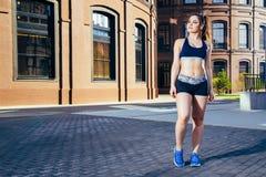 Mulher do esporte da aptidão no sportswear que faz o exercício da aptidão da ioga na rua da cidade fotografia de stock