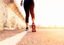 Mulher do esporte que anda para no lado da estrada Conceito da etapa imagem de stock