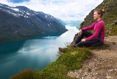Mulher do esporte que caminha em Besseggen Os caminhantes apreciam o lago bonito e o bom tempo em Noruega Imagens de Stock