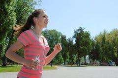 Mulher do esporte que corre e que escuta a música Fotografia de Stock