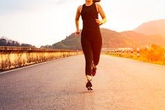 Mulher do esporte que corre em uma estrada Treinamento da mulher da aptidão no por do sol fotos de stock