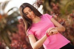 Mulher do esporte que verifica seu relógio Imagem de Stock