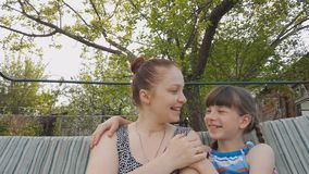 Mulher do estilo de vida com sua filha que senta-se em um balanço do jardim, em relações de família entre pais e em crianças vídeos de arquivo