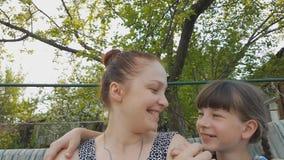 Mulher do estilo de vida com sua filha que senta-se em um balan?o do jardim, em rela??es de fam?lia entre pais e em crian?as vídeos de arquivo
