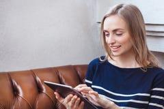 Mulher do estilo de vida da cidade do café na mensagem de texto texting da tabuleta no assento do app da tabuleta interno no café Imagem de Stock